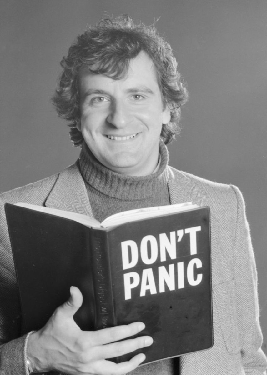"""Here author Douglas Adams poses holding a copy of the book which has """"Don't Panic"""" written on the front cover. 29th November 1978. (Photo by Daily Mirror/Mirrorpix/Mirrorpix via Getty Images)"""