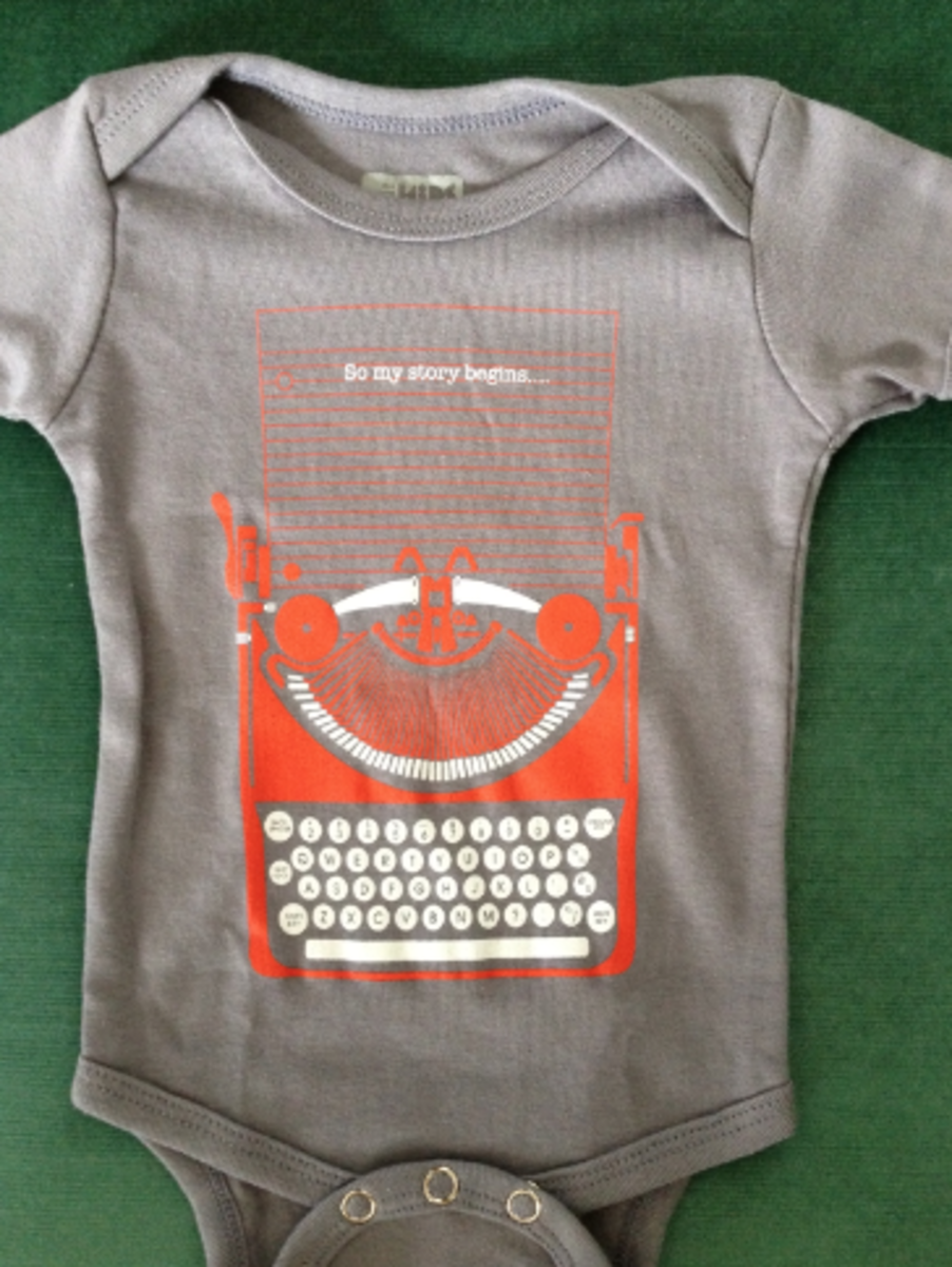 "Best baby outfit of all time. It is a typewriter and text that says ""So my story begins..."""